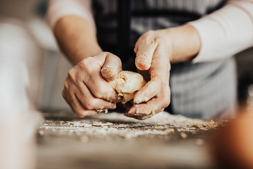 Close-up of woman's hands kneading dough 649219742