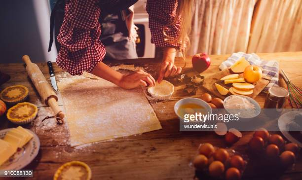 close-up of woman's hands making apple pies in rustic kitchen - old fashioned thanksgiving stock photos and pictures