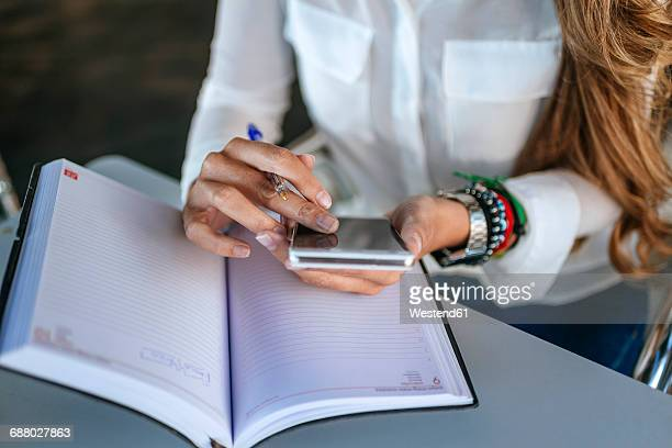 Close-up of womans hands using a smartphone and a notebook