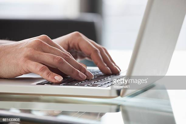 Close-up of womans hands using laptop