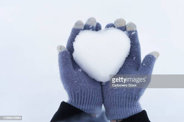 close-up of woman's hands with gloves holding a snow heart - formal glove stock pictures, royalty-free photos & images