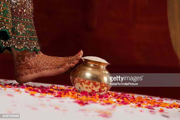 close-up of womans leg and vase filled with rice - indian female feet stock pictures, royalty-free photos & images