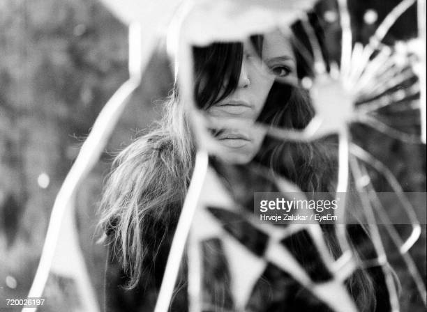 Close-Up Of Womans Reflection In Broken Glass
