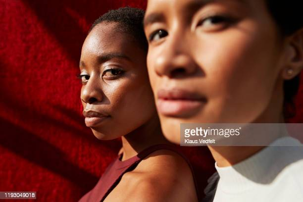 close-up of women against red wall - brown eyes stock pictures, royalty-free photos & images