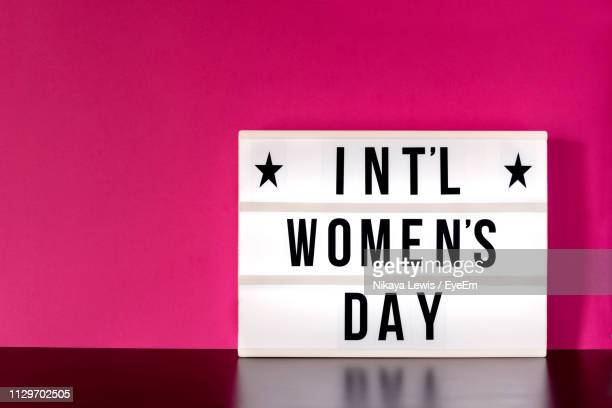 close-up of womens day sign against pink wall - internationale vrouwendag stockfoto's en -beelden