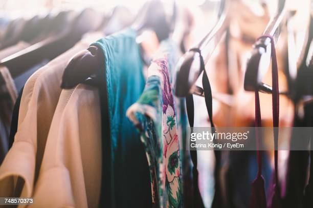 close-up of womenswear hanging on coathangers in store - womenswear stock pictures, royalty-free photos & images