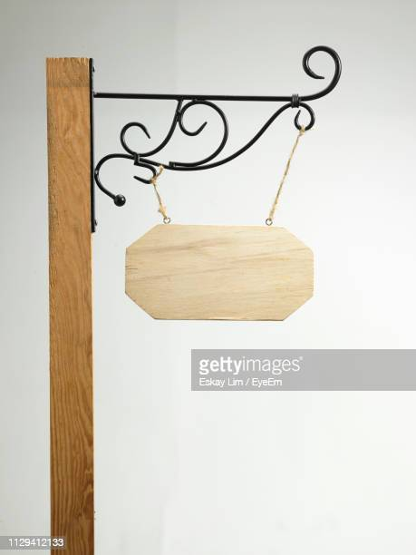 Close-Up Of Wood Hanging On Pole Against White Background