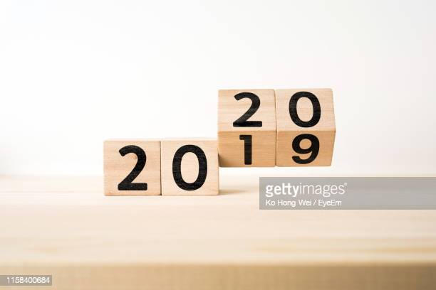 close-up of wooden blocks with 2019 2020 number on table against white background - 2020年 ストックフォトと画像