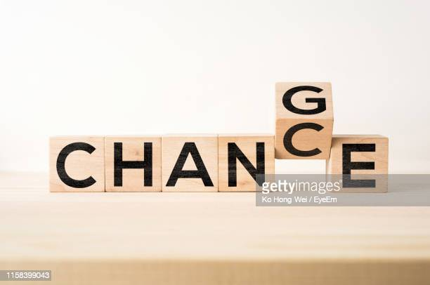 close-up of wooden blocks with change chance text on table against white background - reforma assunto imagens e fotografias de stock