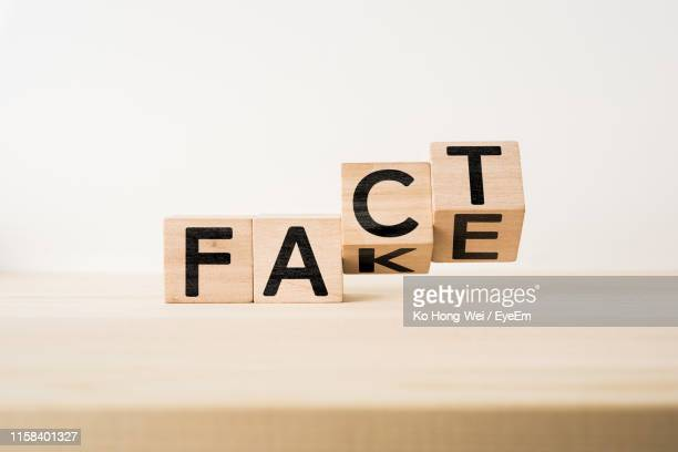 close-up of wooden blocks with fact fake text on table against white background - kunstmatig stockfoto's en -beelden
