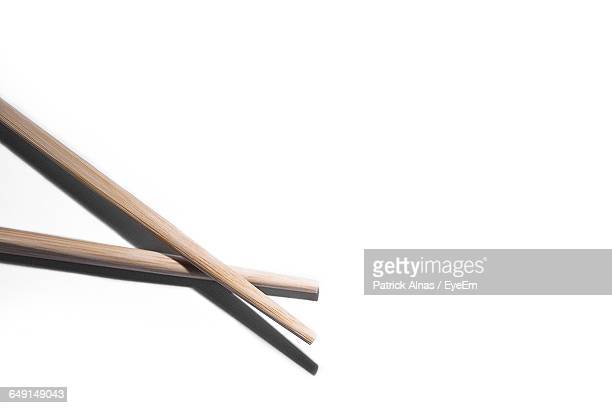 Close-Up Of Wooden Chopsticks On White Background