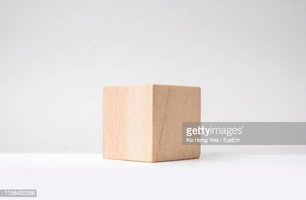 close-up of wooden cube against white background - 立方体 ストックフォトと画像