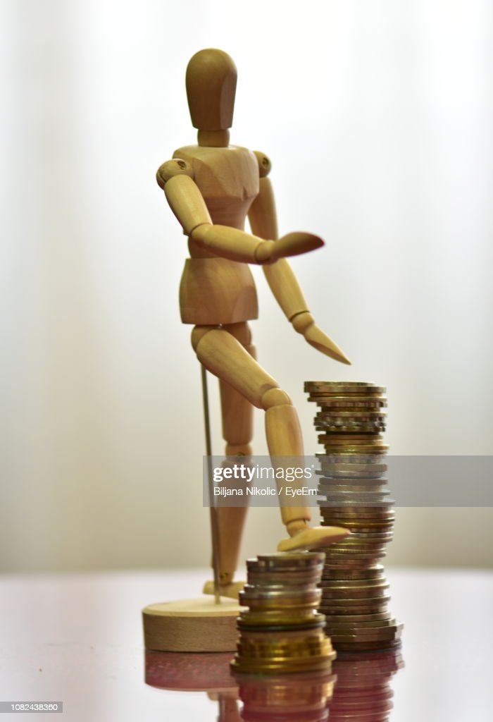 Close-Up Of Wooden Figurine With Coins On Table : Stock Photo