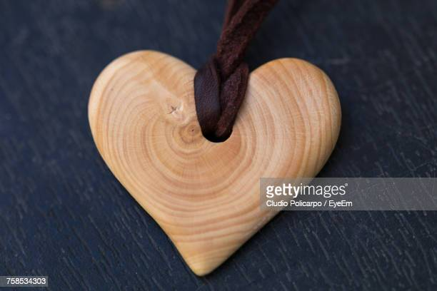 Close-Up Of Wooden Heart Shape Locket On Table