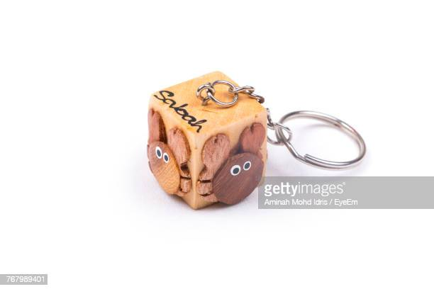 Close-Up Of Wooden Keyring Charm Over White Background