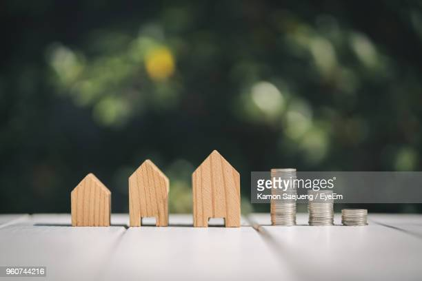 close-up of wooden model homes and stacked coins on table - housing development stock pictures, royalty-free photos & images