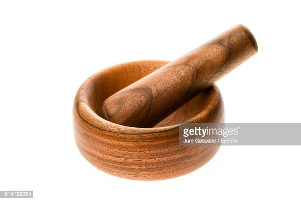 Close-Up Of Wooden Mortar And Pestle Against White Background