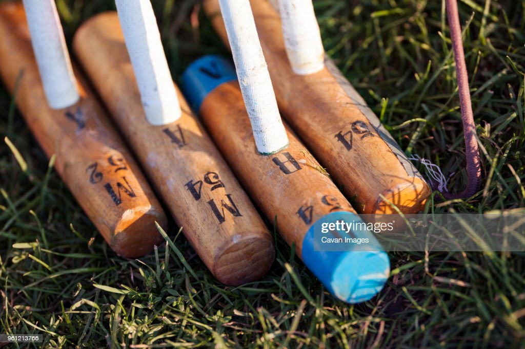 Close-up of wooden polo mallets on grassy field : Stock Photo