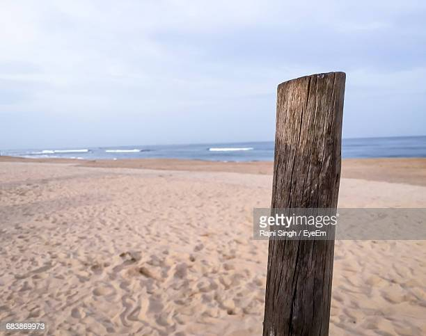 Close-Up Of Wooden Post At Beach Against Sky