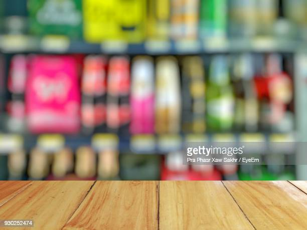 close-up of wooden table against bookshelf - shelf stock pictures, royalty-free photos & images