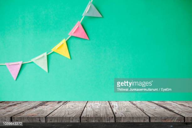 close-up of wooden table against colorful bunting flag on wall - bunting stock pictures, royalty-free photos & images