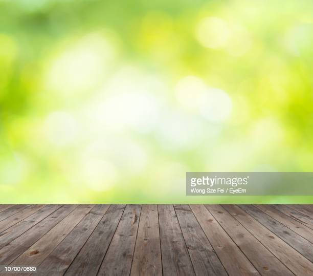 close-up of wooden table against defocused pattern - 後ろボケ ストックフォトと画像