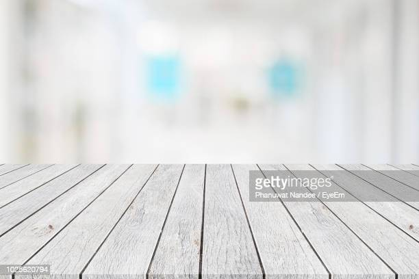 close-up of wooden table against illuminated lights - white wood stock pictures, royalty-free photos & images