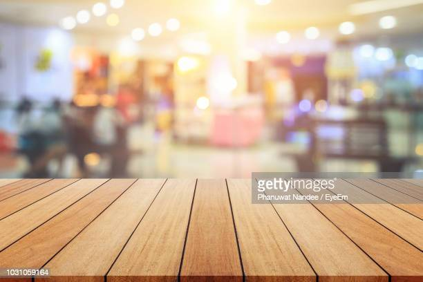 close-up of wooden table against illuminated lights - incidental people stock pictures, royalty-free photos & images