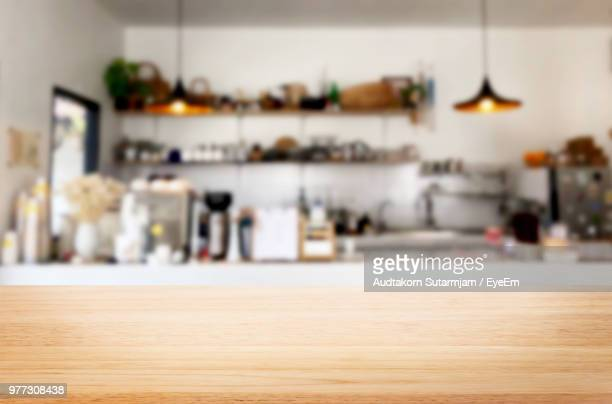 close-up of wooden table against kitchen - onscherpe achtergrond stockfoto's en -beelden