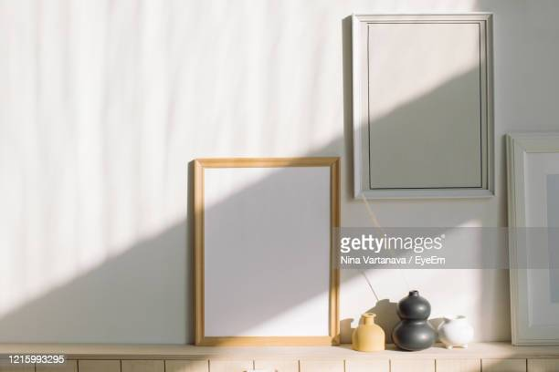close-up of wooden table against wall at home - beige foto e immagini stock