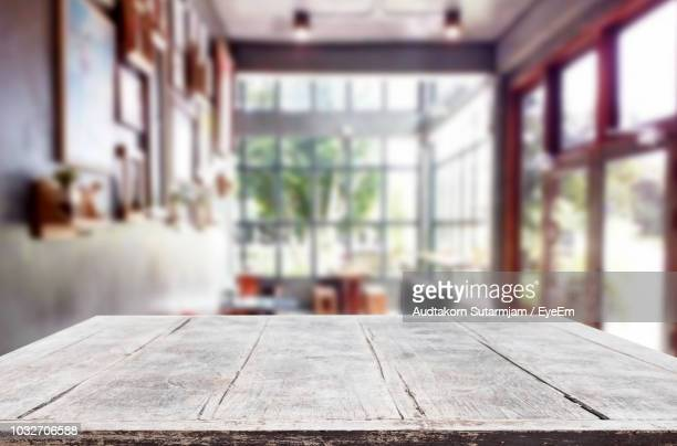 close-up of wooden table against window at home - tafel stockfoto's en -beelden