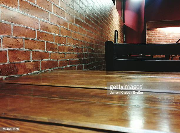 Close-Up Of Wooden Table And Chair By Brick Wall At Restaurant