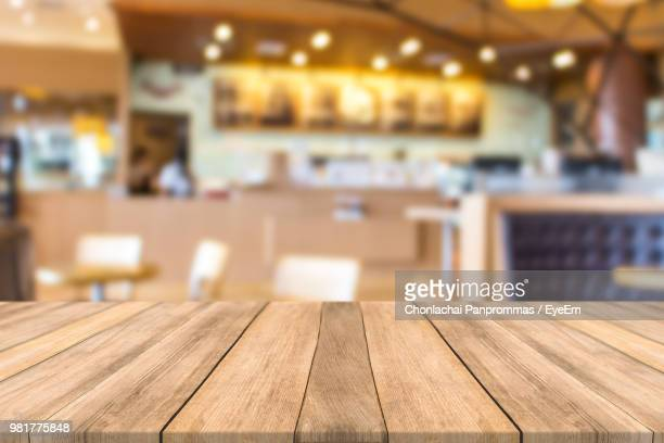 close-up of wooden table in cafe - onscherpe achtergrond stockfoto's en -beelden