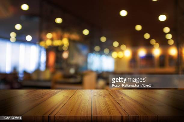 close-up of wooden table in illuminated restaurant - focus on foreground stock pictures, royalty-free photos & images