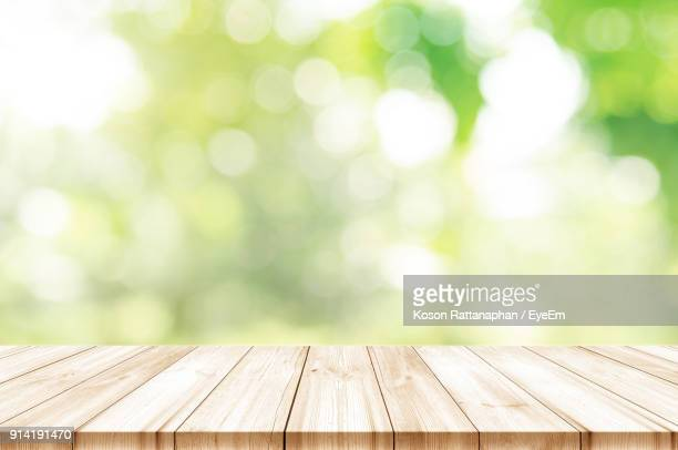 close-up of wooden table outdoors - onscherpe achtergrond stockfoto's en -beelden