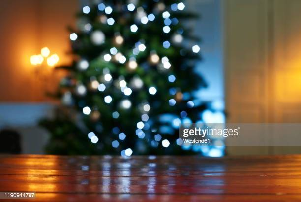 close-up of wooden table with illuminated christmas tree in background at home - table stock-fotos und bilder
