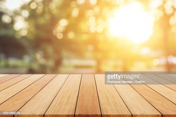 close-up of wooden table with trees in background - table stock pictures, royalty-free photos & images