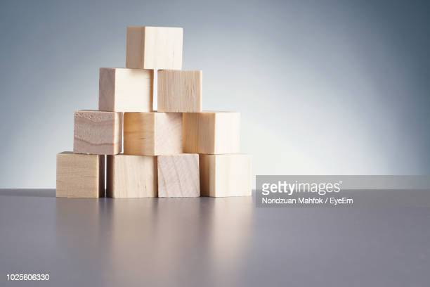 Close-Up Of Wooden Toy Blocks On Table Against Wall