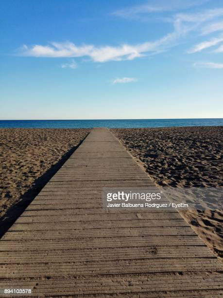 Close-Up Of Wooden Walkway By Sea Against Sky