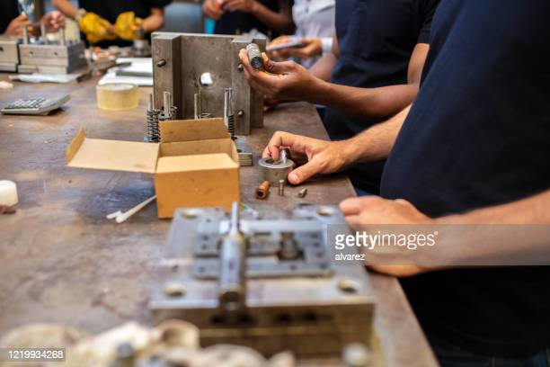 close-up of workers assembling press tools in tool room - spare part stock pictures, royalty-free photos & images