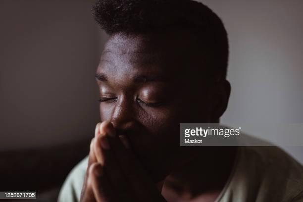 close-up of worried man with eyes closed at home - met de ogen dicht stockfoto's en -beelden