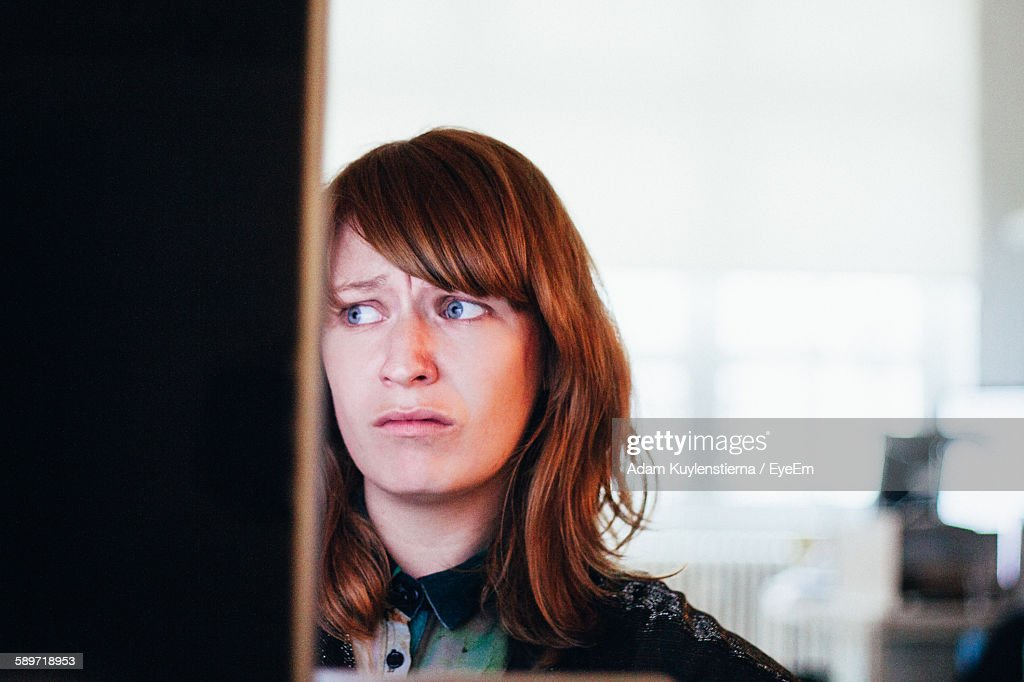 Close-Up Of Worried Woman While Sitting At Computer Desk In Office : Stock Photo