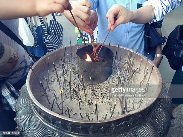Close-Up Of Worshippers Igniting Incense Sticks On Bronze Urn At Todaiji Temple