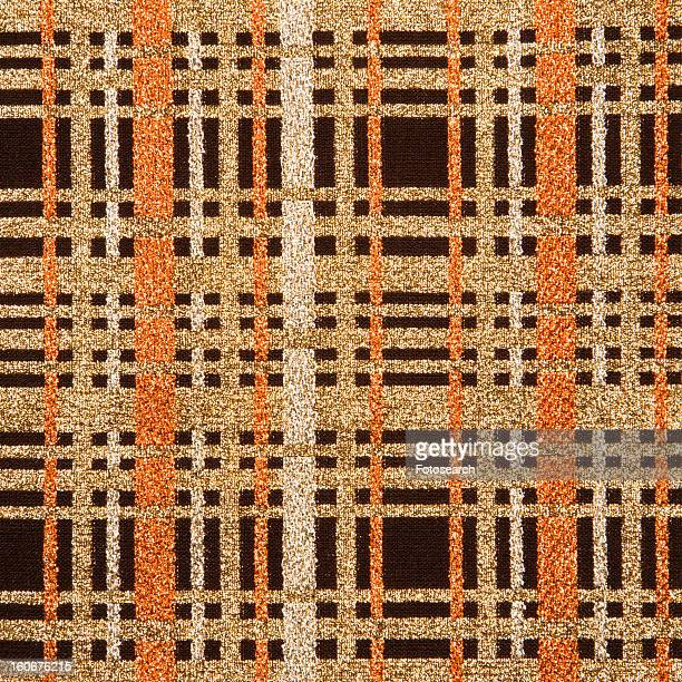 Close-up of woven vintage fabric with brown and gold crossbar pattern