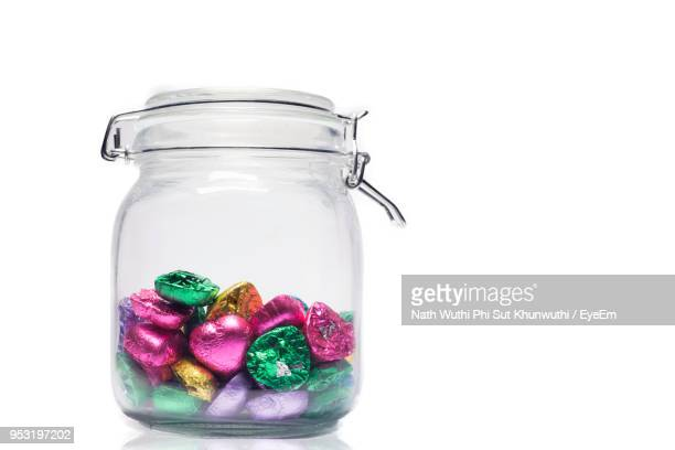 close-up of wrapped chocolates in jar against white background - indulgence stock photos and pictures