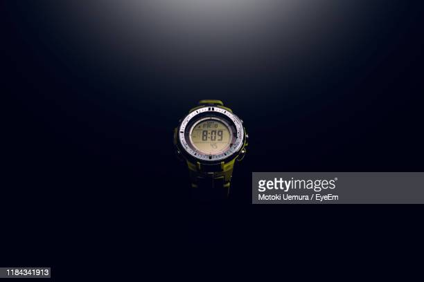 close-up of wristwatch against black background - wrist watch stock pictures, royalty-free photos & images