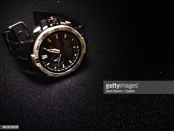 close-up of wristwatch on black surface - wrist watch stock pictures, royalty-free photos & images