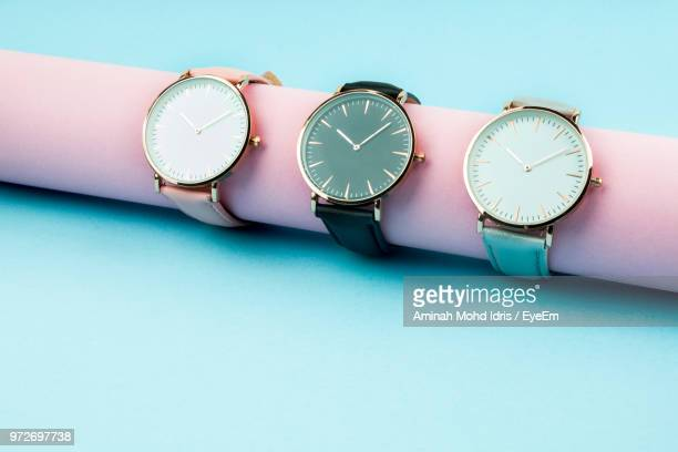 close-up of wristwatches on pink roll against blue background - wrist watch stock pictures, royalty-free photos & images