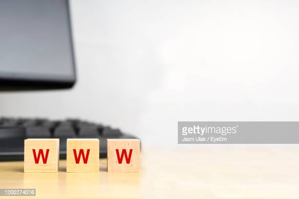 close-up of www text on wooden block by computer on table - www stock pictures, royalty-free photos & images