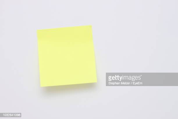 close-up of yellow adhesive note against white background - adhesive note stock pictures, royalty-free photos & images